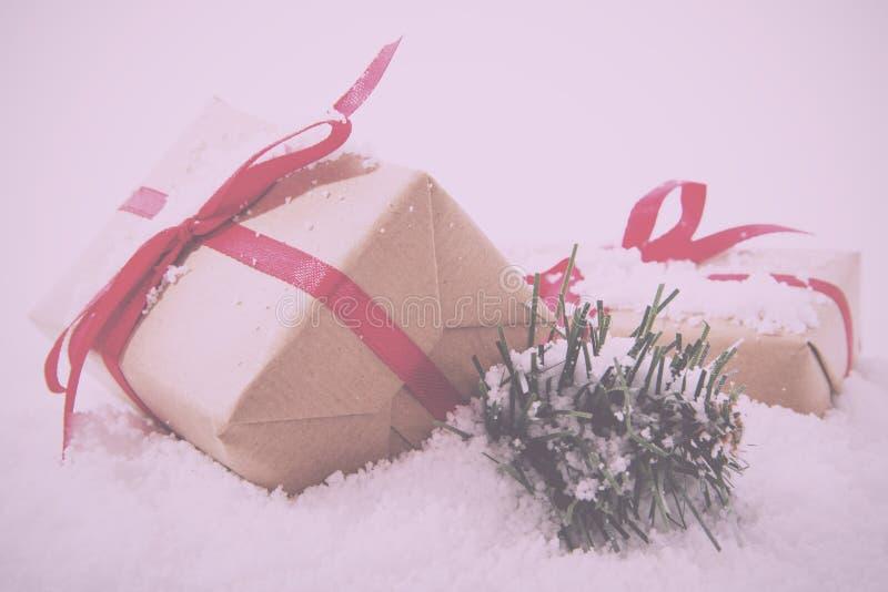 Regalos de Navidad en papel marrón con el vintage rojo de la cinta retro imagenes de archivo
