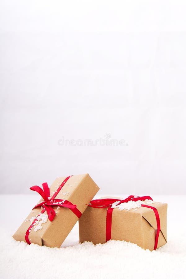 Regalos de Navidad en papel marrón con la cinta roja imagen de archivo