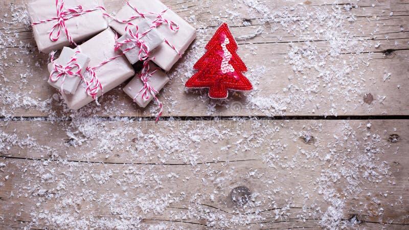 Regalos de Navidad envueltos y árbol decorativo de la piel en la madera envejecida foto de archivo libre de regalías
