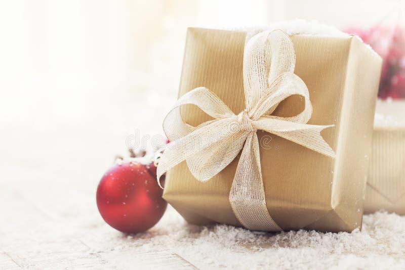 Regalos de Navidad o regalos con las decoraciones elegantes del arco y de la Navidad en fondo nevoso brillante imagen de archivo libre de regalías