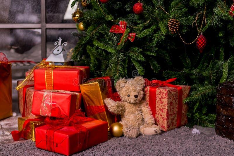 Regalos debajo del árbol de navidad, del oso y de las cajas, el concepto del juguete de un Año Nuevo casero acogedor Oso que espe fotos de archivo libres de regalías