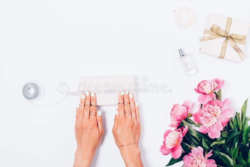 Regalos del embalaje de la mujer al lado de las flores rosadas de la peonía fotografía de archivo libre de regalías