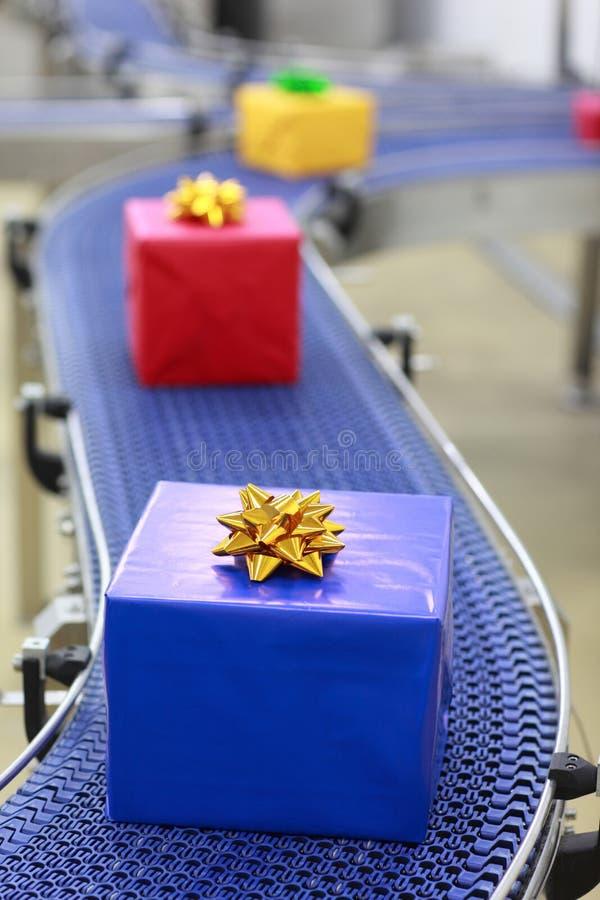 Regalos en la banda transportadora en fábrica de los regalos de Navidad fotos de archivo
