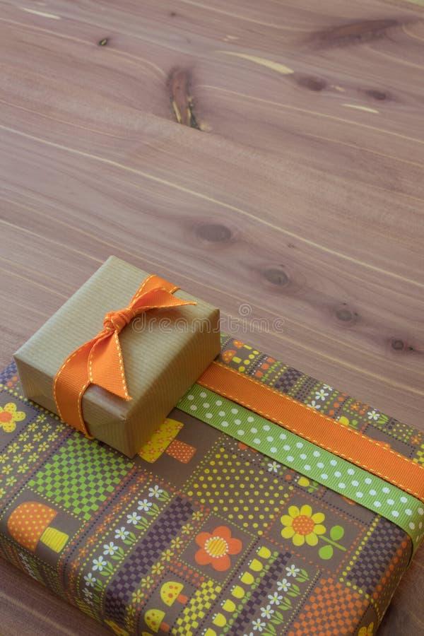 Regalos en papel retro con las flores y las setas, marrón y verde anaranjados, diagonal en la tabla de madera neutral imagen de archivo