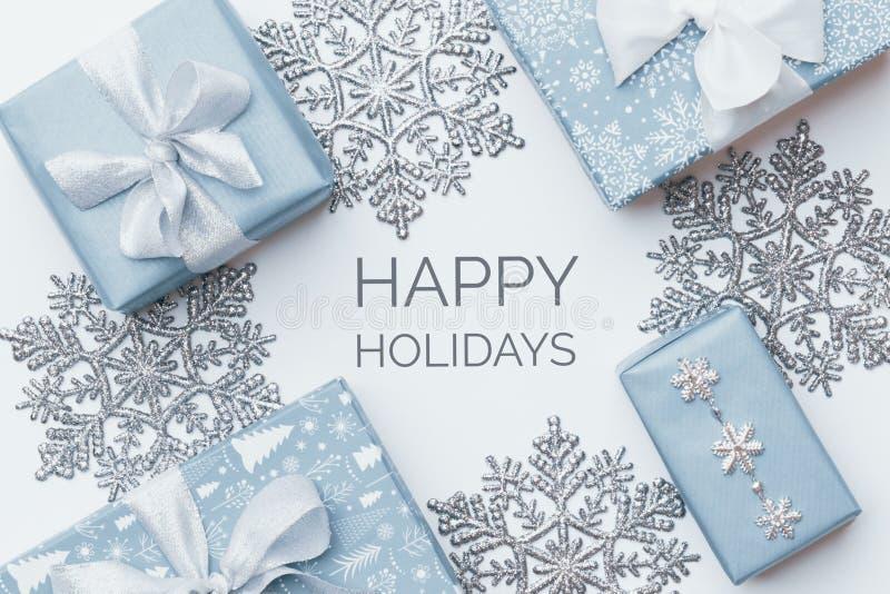 Regalos hermosos de la Navidad y copos de nieve de plata aislados en el fondo blanco Cajas envueltas coloreadas azul en colores p imagen de archivo