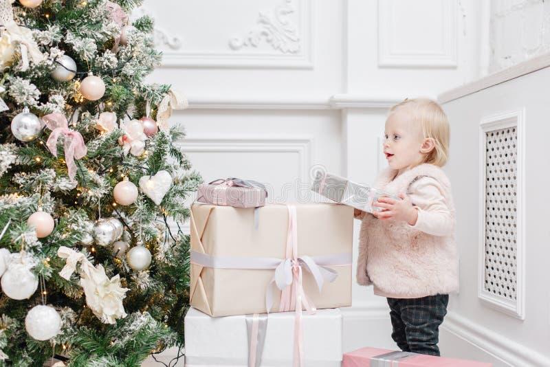 Regalos lindos del bebé y de la Navidad Pequeño niño que se divierte cerca del árbol de navidad en sala de estar Feliz Navidad de fotos de archivo