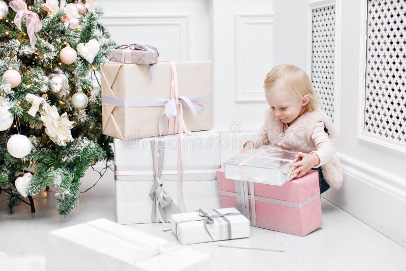 Regalos lindos del bebé y de la Navidad Pequeño niño que se divierte cerca del árbol de navidad en sala de estar Feliz Navidad de fotografía de archivo