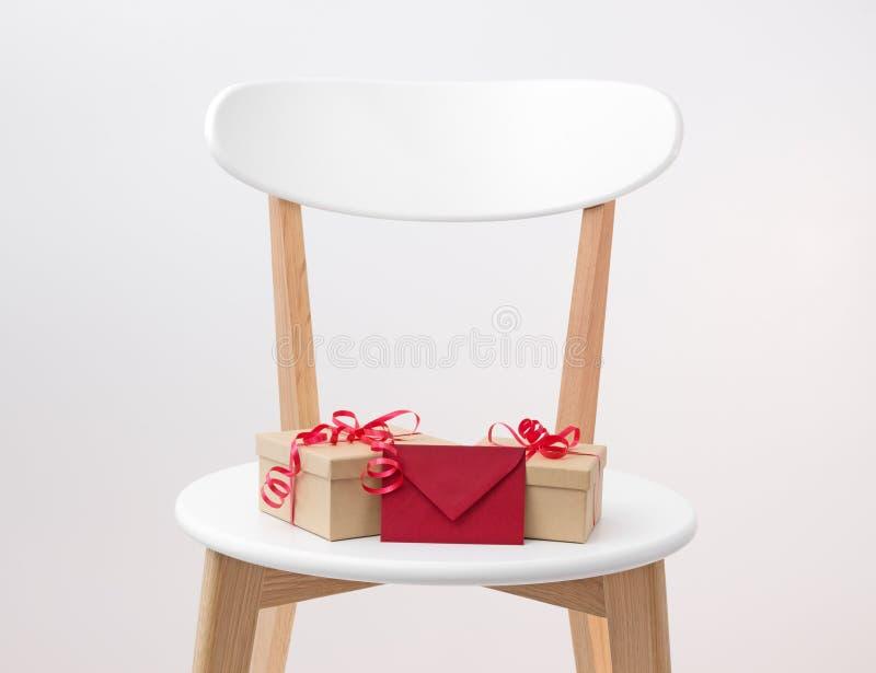 Regalos y sobre rojo en una silla de madera imagen de archivo