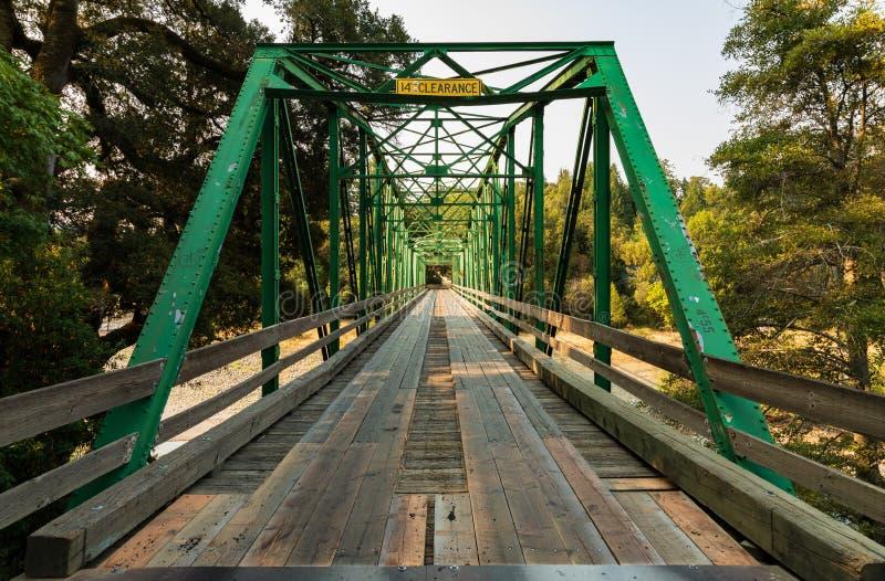 Regard à travers le vieux un pont suspendu vert d'acier de ruelle image libre de droits