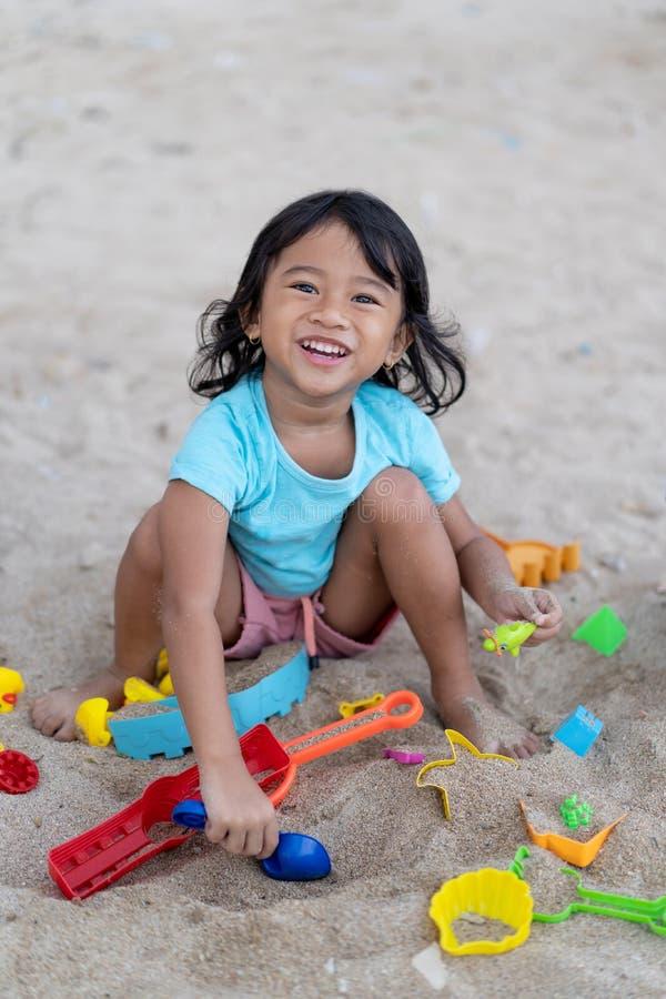Regard asiatique de petite fille à la caméra en jouant le château de sable photos stock