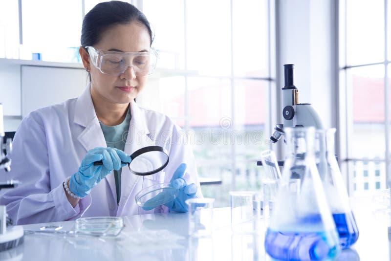 Regard asiatique de scientifique de femme par la loupe photographie stock libre de droits