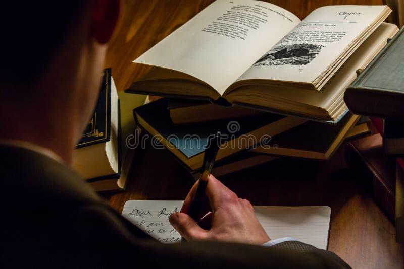 Regard au-dessus de l'épaule d'un homme écrivant une lettre tout en lisant les ouvrages littéraires photographie stock