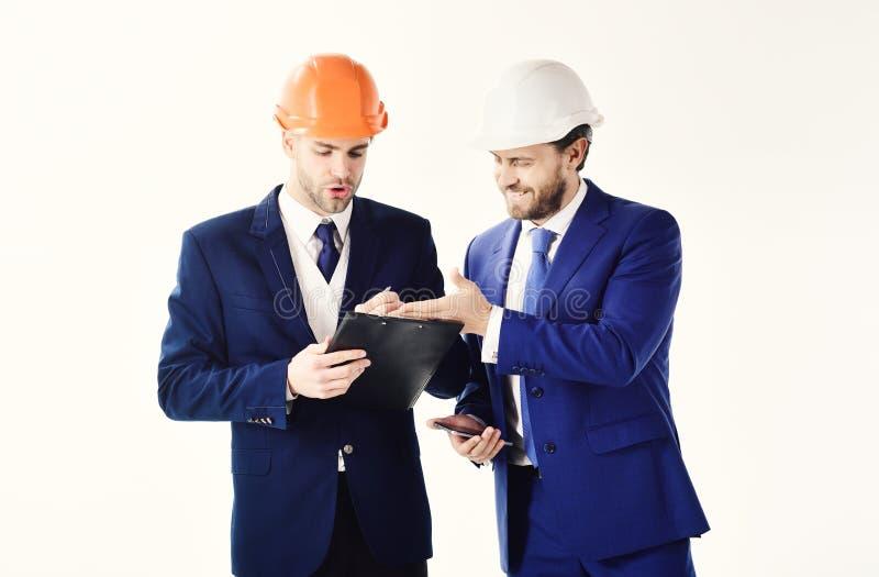 Regard d'associés au plan de bâtiment Ingénieurs avec des barbes et des visages heureux Les architectes discutent le projet entre photographie stock