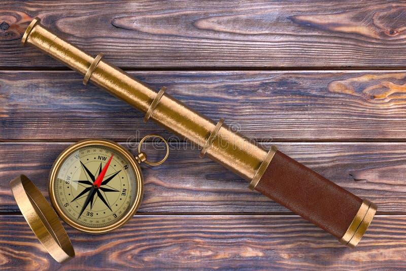 Regard d'or de télescope de vintage avec la boussole au-dessus du Tableau en bois image stock