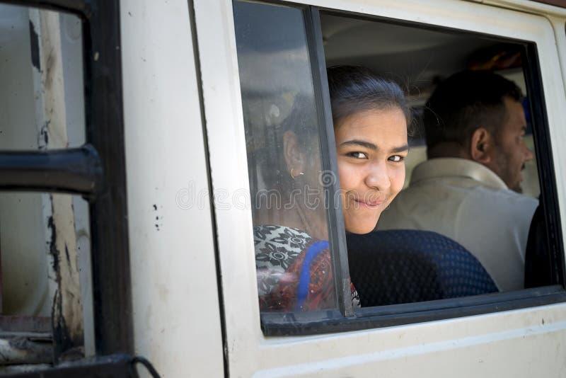 Regard de dame assez jeune hors de la fenêtre de voiture souriant, Himachal Pradesh photographie stock