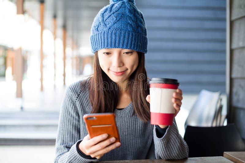 Regard de femme au téléphone portable au café extérieur photos stock