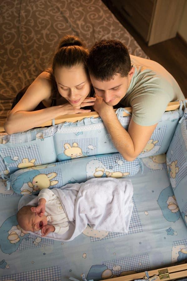 Regard de femme et d'homme à nouveau-né Cris de garçon dans sa huche Maman, papa et chéri Portrait de jeune famille Vie de famill images libres de droits