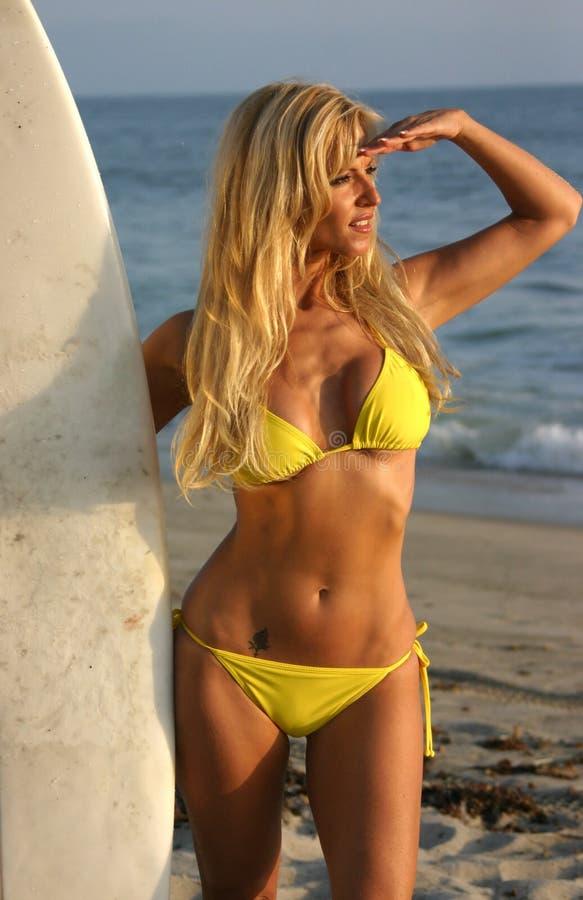 regard de la femme de planche de surfing de coucher du soleil photographie stock