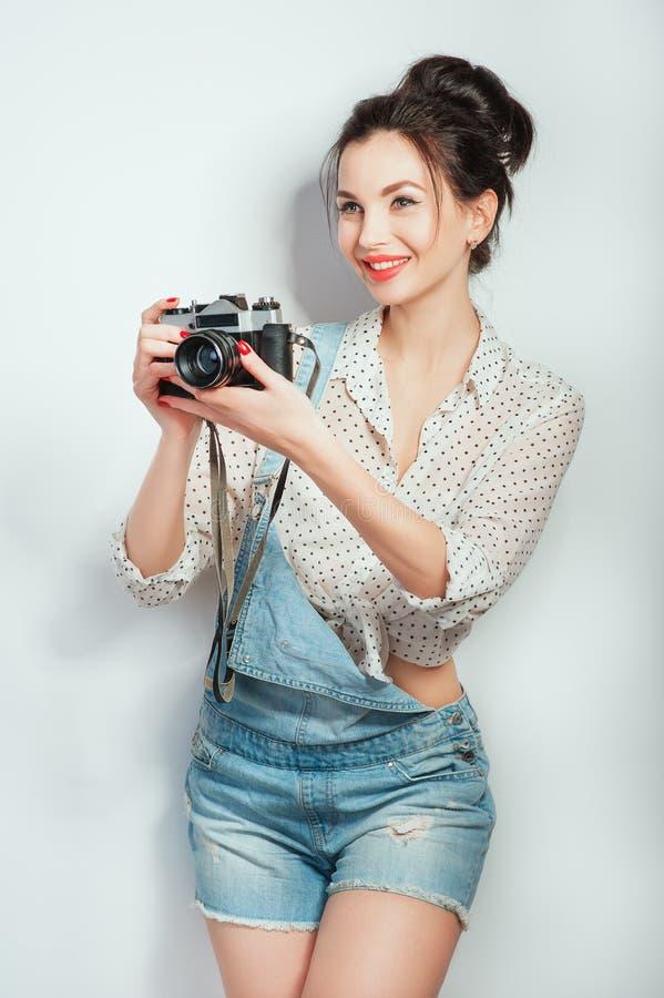 Regard de mode, modèle assez frais de jeune femme avec la caméra de film portant dans des vêtements de denim posant sur le mur bl photographie stock libre de droits