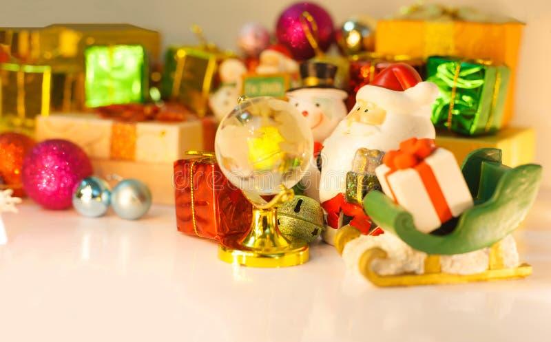 Regard de Santa Claus et de bonhomme de neige au globe pour que les bons enfants livrent les cadeaux, fond avec les boîtes décoré images stock
