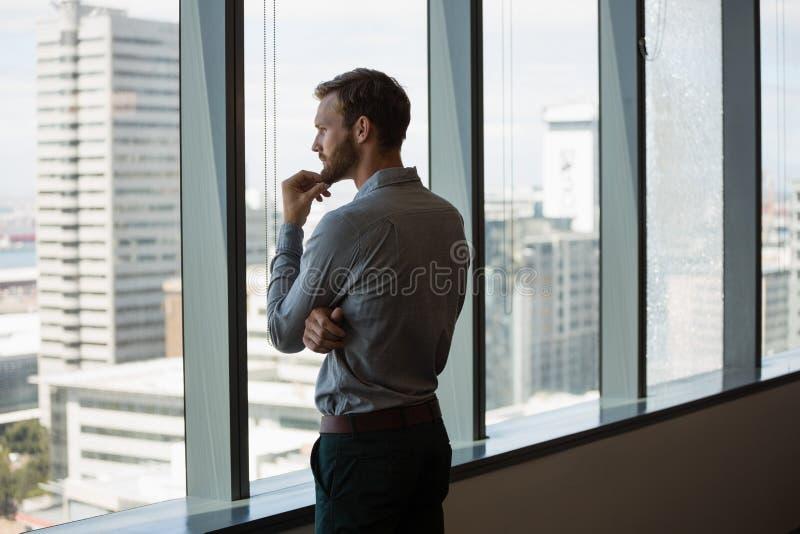 Regard exécutif masculin par la fenêtre dans le bureau images stock
