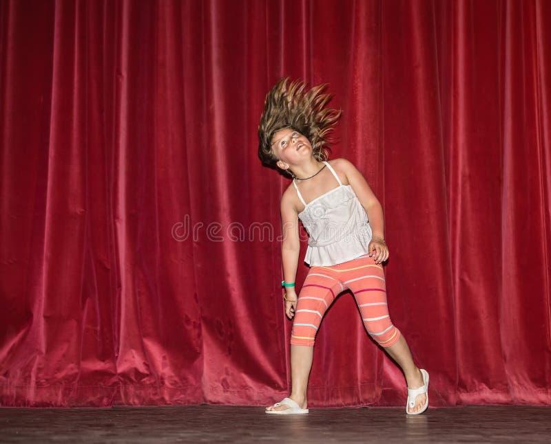 Regard heureux et joyeux de petite fille à son mouvement de cheveux tandis qu'elle fonctionnement, dansant sur l'étape de nuit co photos libres de droits