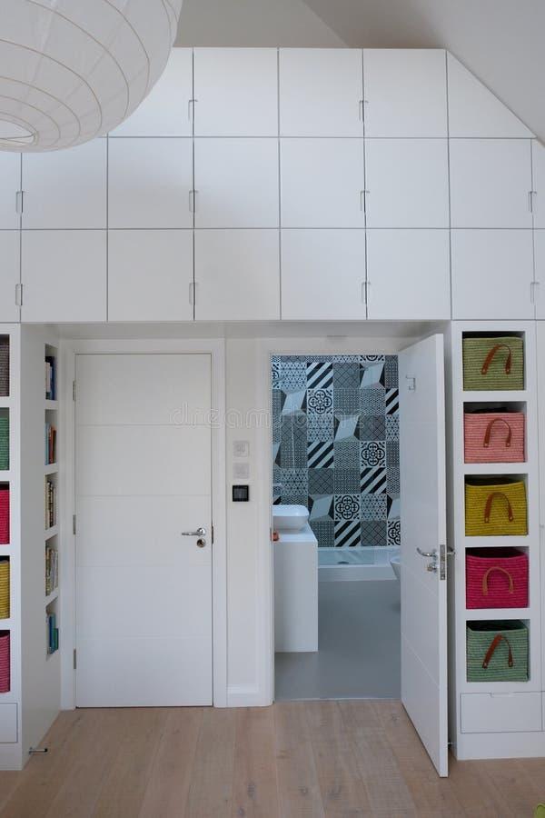 regard intérieur de chambre à coucher remplie de lumière dans la salle de bains d'ensuite avec les tuiles monochromes photo stock