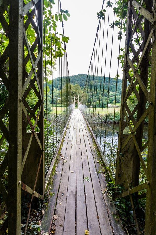 Regard le long du passage couvert en bois de pont suspendu photographie stock libre de droits