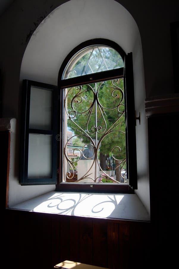 Regard par la fenêtre à déchenchements périodiques arquée ensoleillée à la cour photos libres de droits