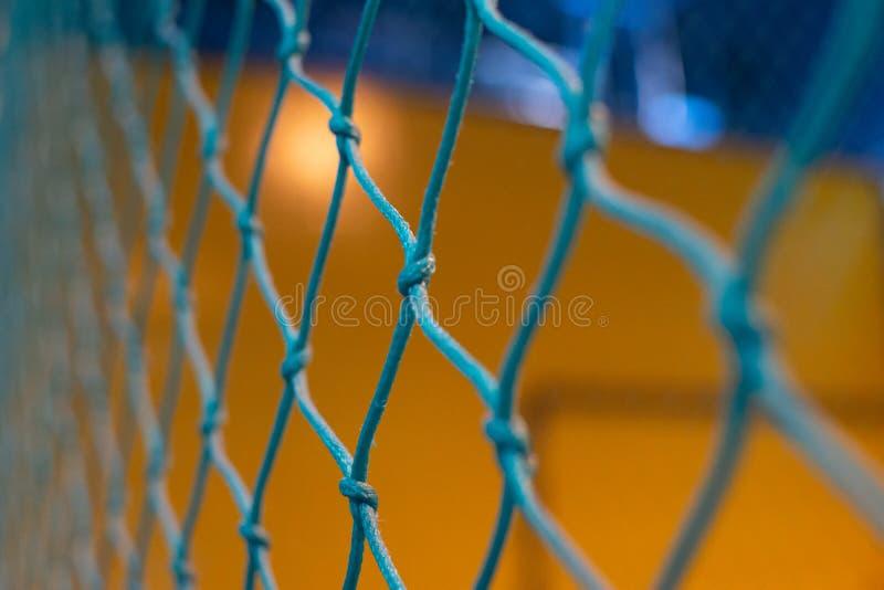 Regard par un filet bleu à un jaune et à un fond bleu brouillés  Jeux, sports, buts, ou concepts image stock