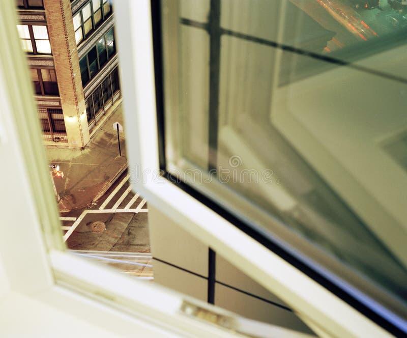 Regard par une rue d'une demi fenêtre ouverte dans NYC photographie stock libre de droits
