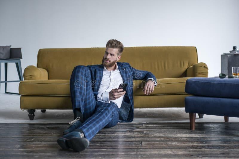 Regard parfait Jeune homme beau dans le plein costume utilisant son téléphone portable tout en se reposant sur le plancher à la m photos stock