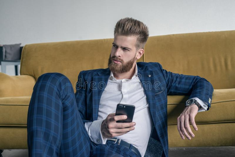 Regard parfait Jeune homme beau dans le plein costume utilisant son téléphone portable tout en se reposant sur le plancher à la m photo libre de droits