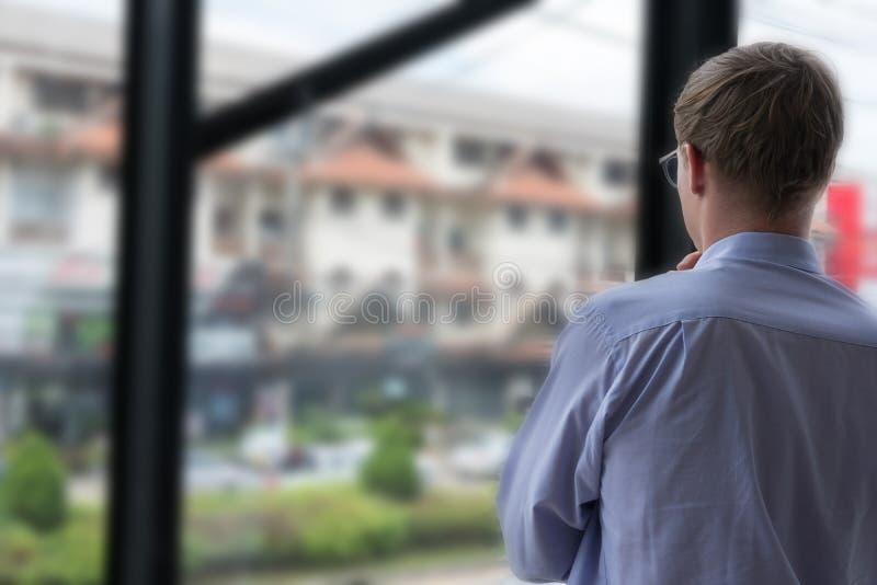 Regard réfléchi d'homme d'affaires à la ville par la fenêtre à l'OE images stock