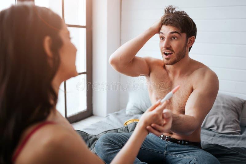 Regard stupéfait de jeune homme à la femme et tenir sa main avec l'essai de grossesse il est heureux Ils se reposent sur le lit R photos libres de droits