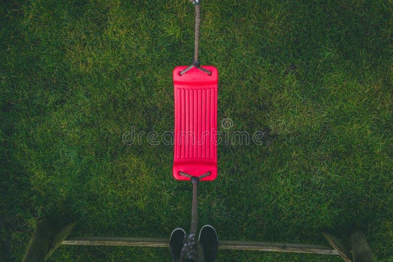 Regard vers le bas sur une oscillation abandonnée rouge dans le jardin images libres de droits