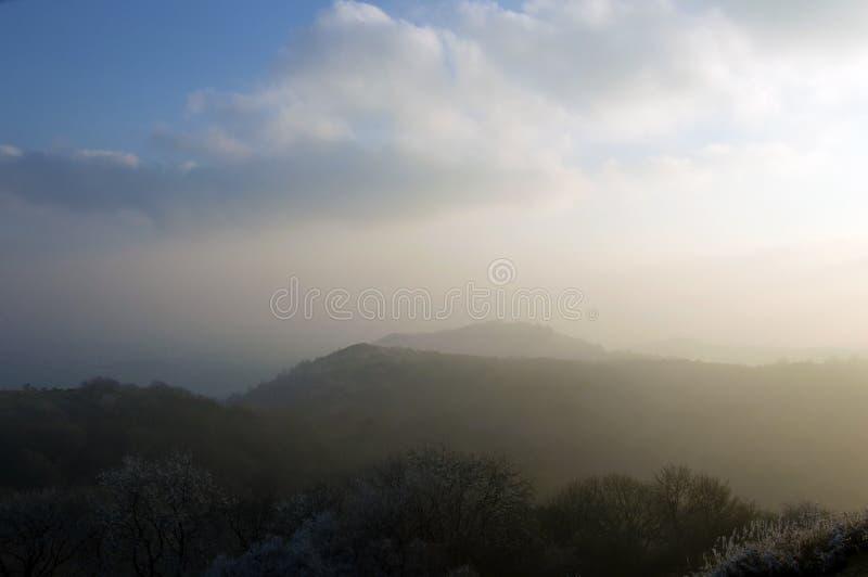 Regardant à travers l'arête et les régions boisées des collines de Malvern un après-midi froid, givré, brumeux Worcestershire, R- images stock