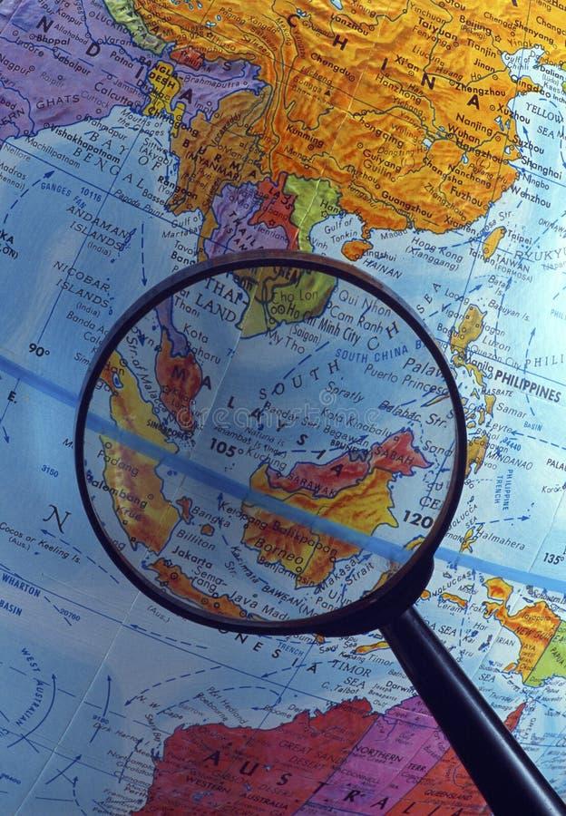 Regardant le globe utilisant la loupe (région asiatique du sud-est) photographie stock