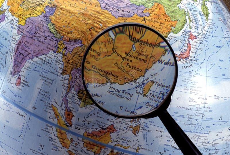 Regardant le globe utilisant la loupe (région de l'Asie) photographie stock libre de droits