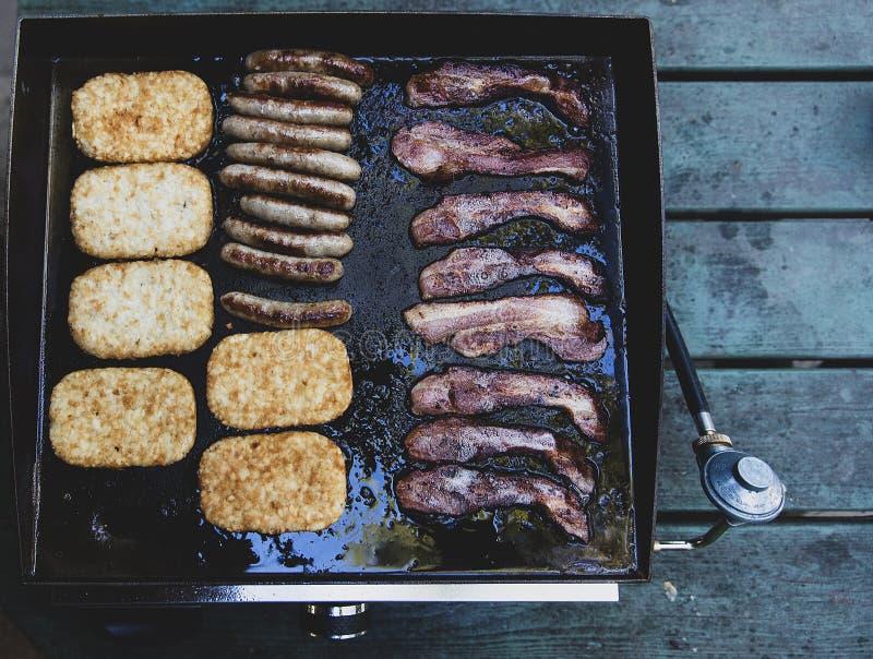Regardant vers le bas sur le gril chaud avec les pommes de terre rissolées, la saucisse et le lard faisant cuire pour le petit dé photo stock