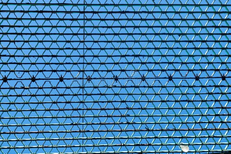 Regardant vers le haut le ciel, par une grille en métal photographie stock