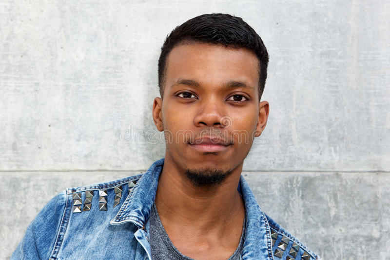 Regarder se tenant prêt de mur d'homme africain attirant à la mode image libre de droits