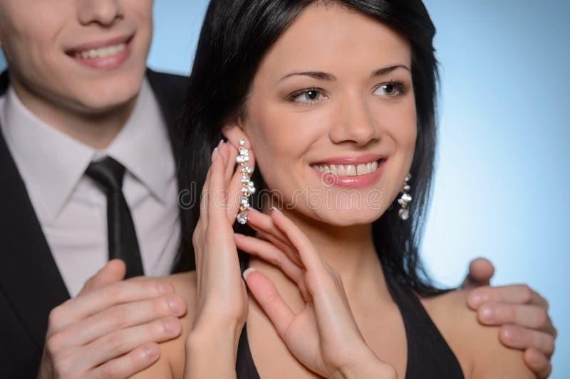 Regarder son cadeau. Belle jeune femme touchant son nouvel earr photos libres de droits