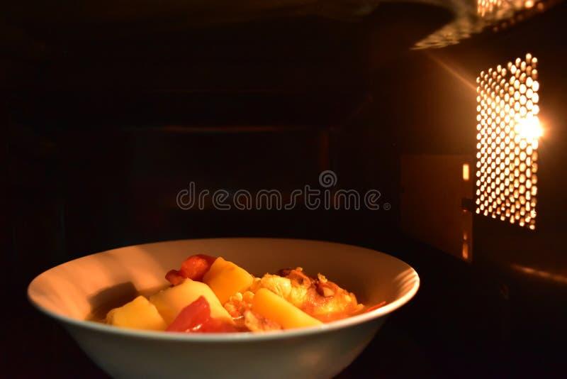 Regardez à l'intérieur du bol blanc de nourriture de micro-onde, dans une atmosphère chaude et un espace supérieur vide pour le t images stock