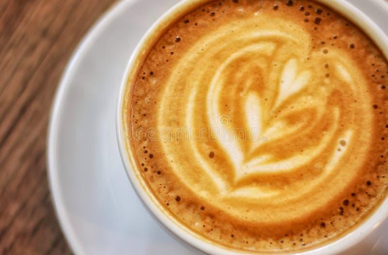 Regardez étroitement le café chaud avec l'art de latte photographie stock libre de droits