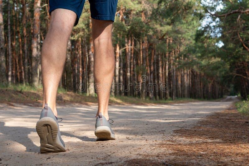 Regardez étroitement les jambes sportives fortes avec les chaussures de course photos stock