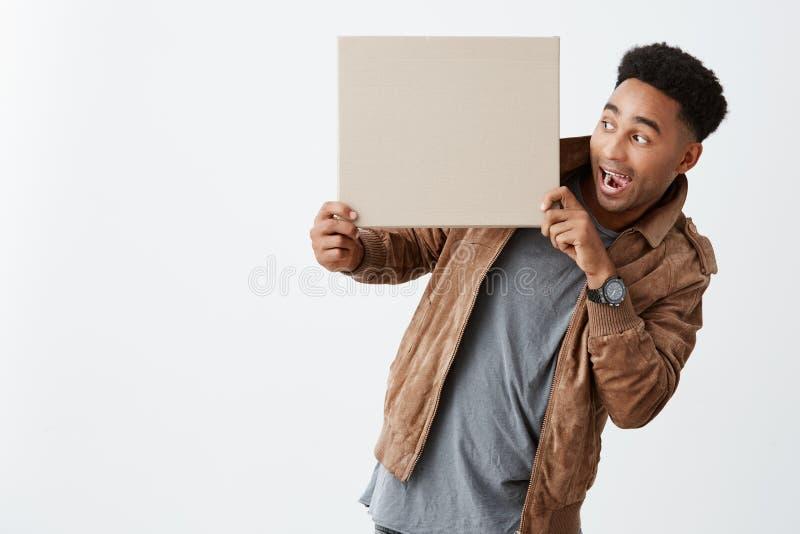 Regardez ceci D'isolement sur le portrait blanc du type drôle à la peau foncée avec la coiffure Afro en hiver occasionnel vêtx se photos stock