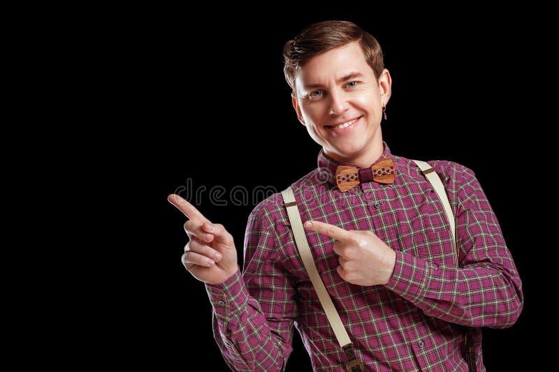 Regardez ceci ! Jeune homme scientifique beau dans le noeud papillon de chemise de vintage dirigeant l'espace de copie et sourian images stock