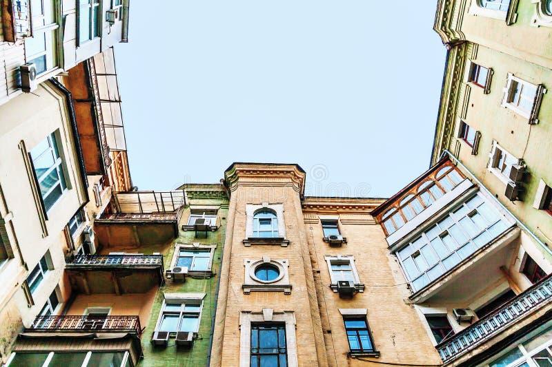 Regardez de bas en haut au ciel, vieilles maisons grandes, puits, balc photos stock