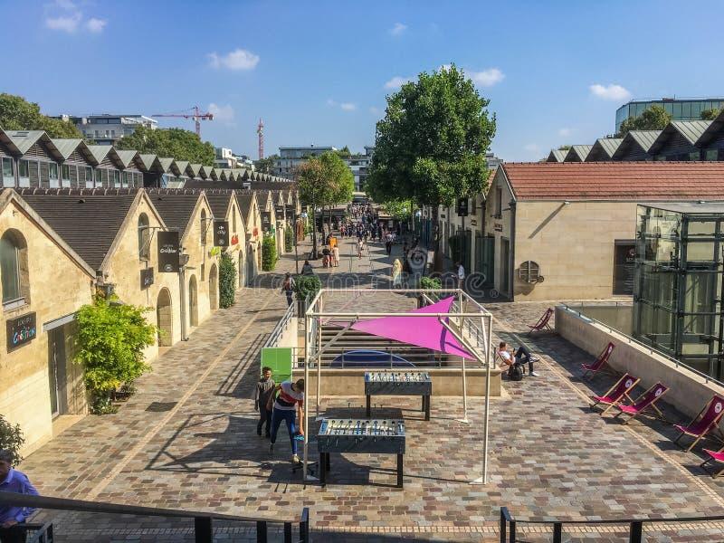 Regardez en bas de la rangée des boutiques et des cafés dans le village de Bercy, Paris, France photographie stock libre de droits